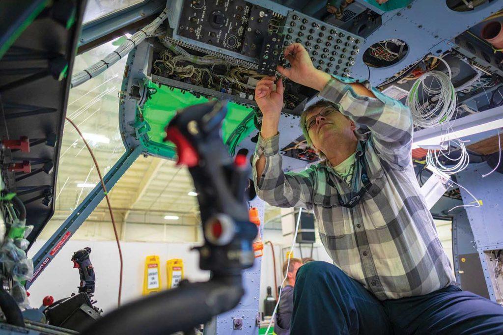 Aeronav Avionics' aircraft maintenance engineer Brent Butowski works on a wiring bus on a Bell 212 at Victoria International Airport. Heath Moffatt Photo