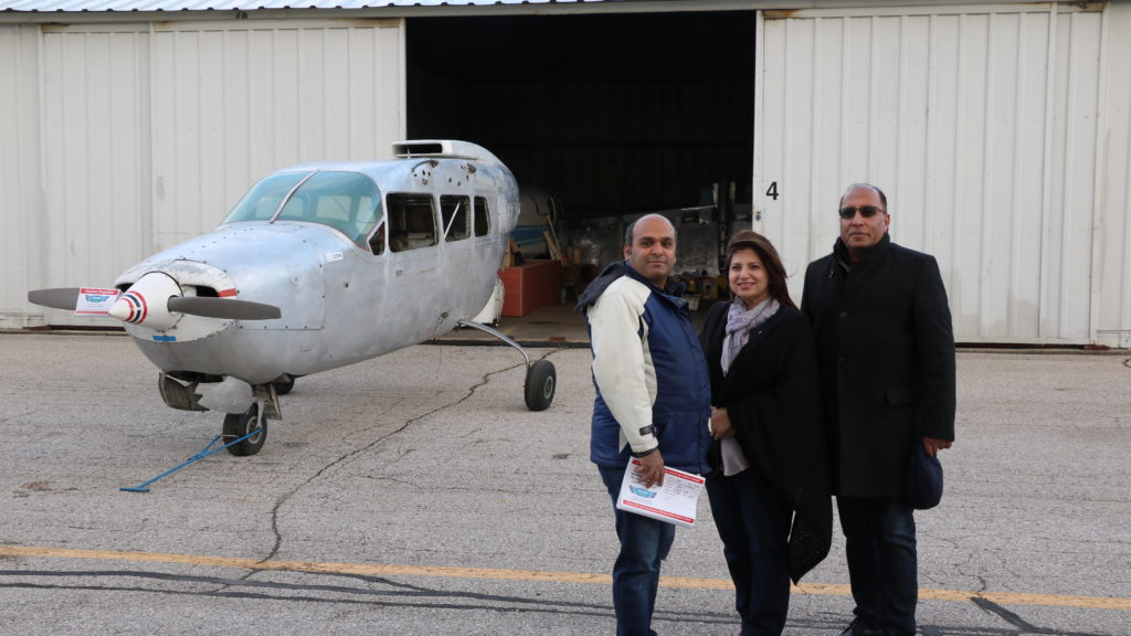 Members of the International Heritage Aviation Recreation Association stand in front of a Cessna Skymaster, which the group is restoring at Region of Waterloo International Airport. From left are Sameer Haqqi, Asifa Baig and Farrukh Baig.