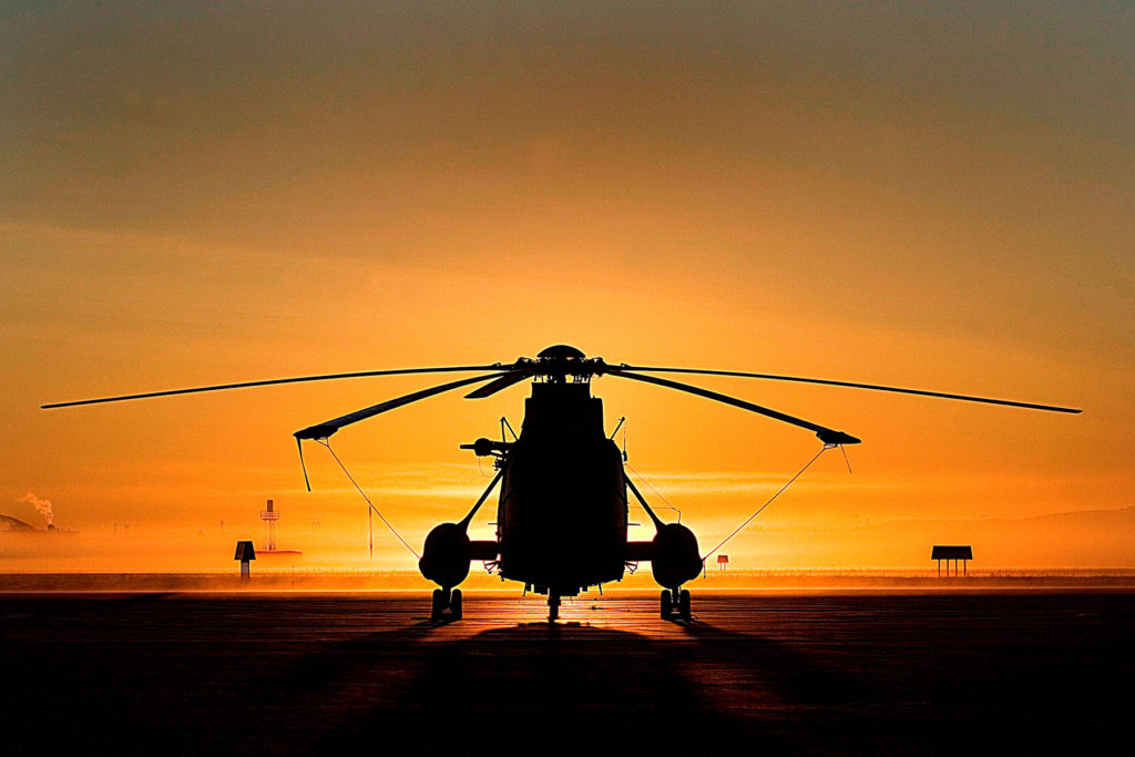 Onboard a ship at sea, a Royal Canadian Air Force CH-124 Sea King helicopter is silhouetted by the sun setting at deck level. Sgt René Dubreuil Photo