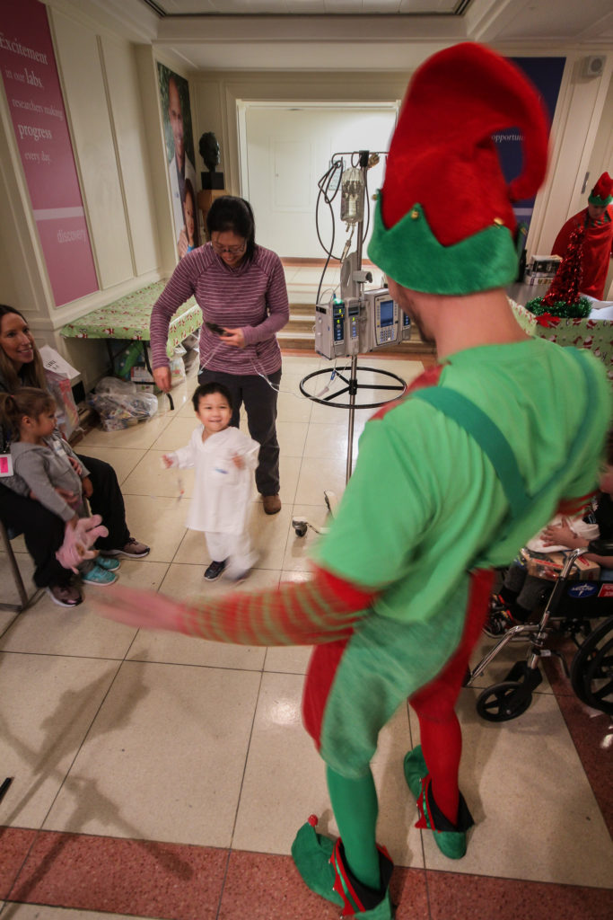 An elf and a young Sick Kids patient take a break from crafting to dance and enjoy the live Christmas music played by a squadron member. Steve Bigg Photo