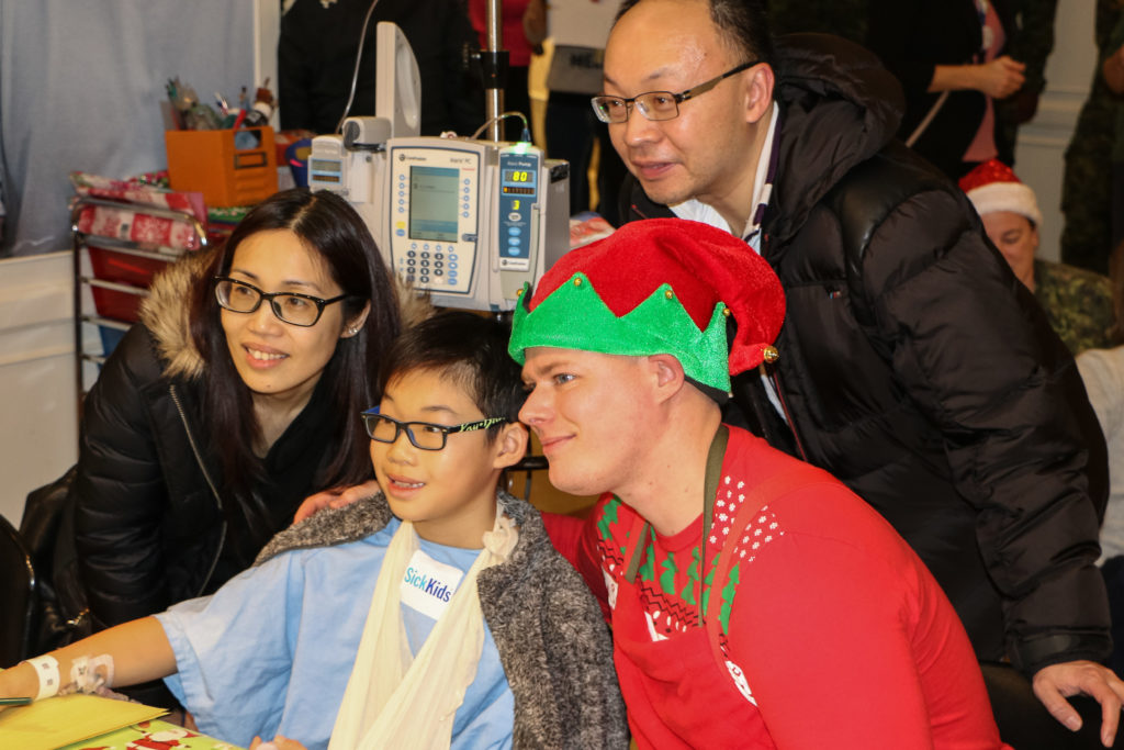 A volunteer elf from 400 Squadron poses with a SickKids patient and his family for a picture during Operation Ho Ho Ho. Steve Bigg Photo