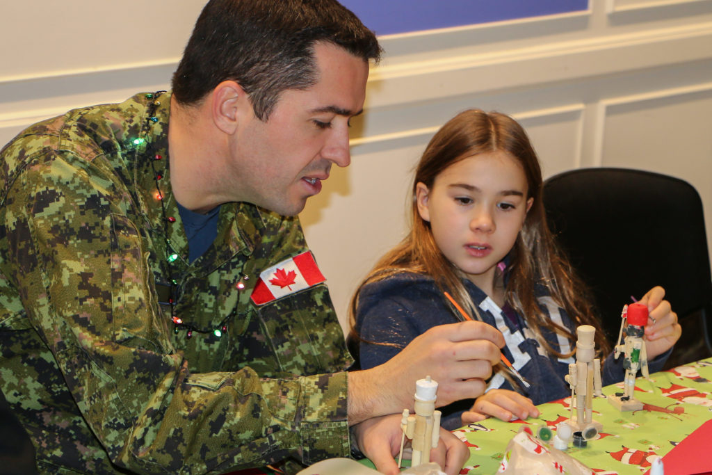 The Commanding Officer of 400 Squadron, LCol Sheink, works with a young Sick Kids patient doing crafts during the squadron's Operation Ho Ho Ho. Steve Bigg