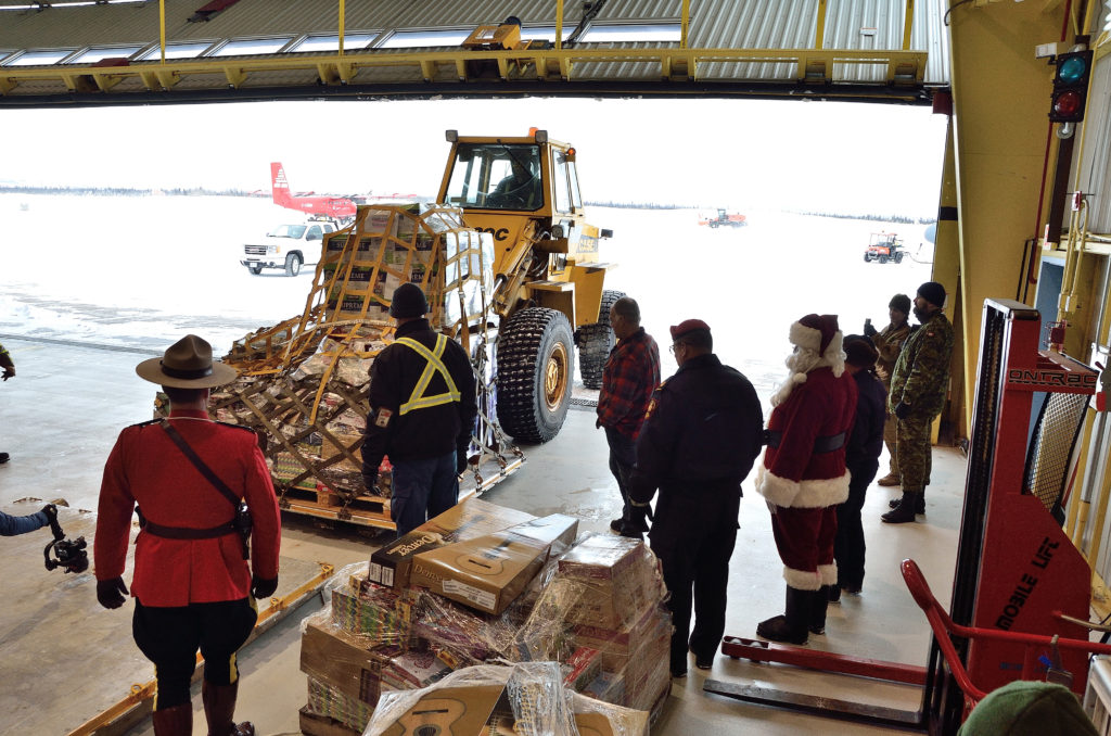 Santa oversees the unloading of toys from a CC-130J Hercules at 5 Wing Goose Bay, N.L., on Dec. 10, 2018. The Herc was carrying toys for children in Canada's most isolated northern communities. MCpl Krista Blizzard Photo