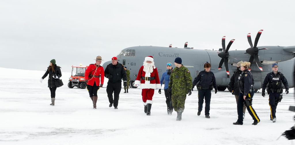 Santa, RCMP and RCAF personnel walk across the snowy tarmac at 5 Wing Goose Bay, N.L., on Dec. 10, 2018, following the arrival of a CC-130J Hercules carrying toys for the RCMP's annual Toys for the North campaign. MCpl Krista Blizzard Photo