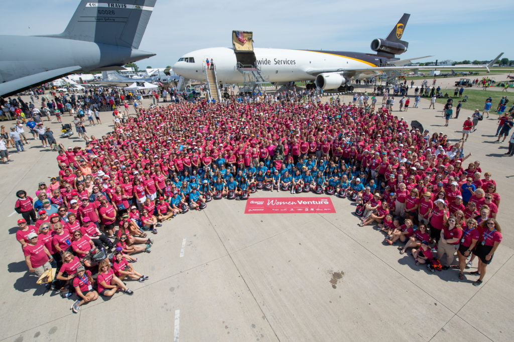 Women aviators gather for a group photo at EAA WomenVenture wearing T-shirts dedicated to the event.
