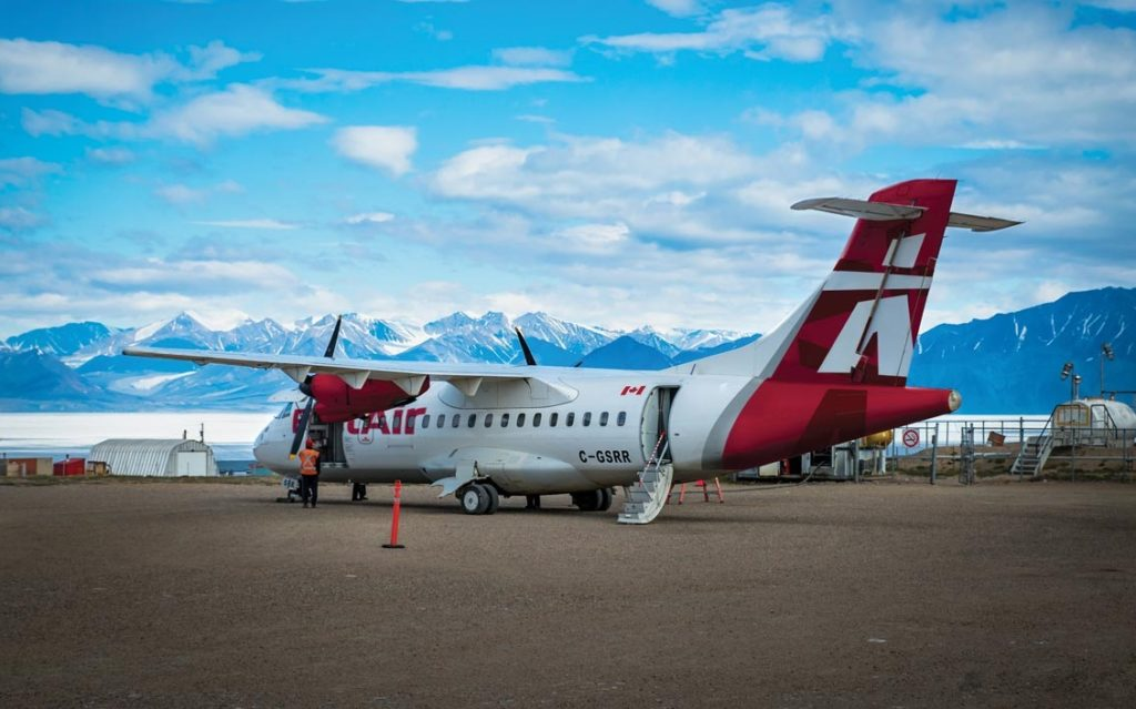 photo of airplane with mountains in the background