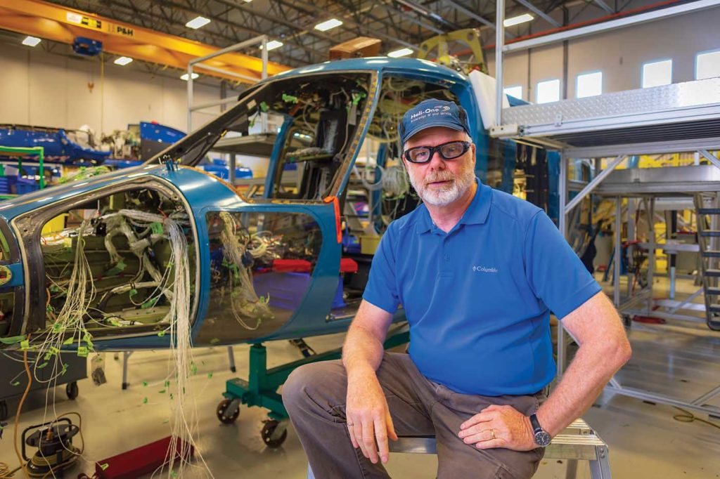 Alan Stewart, senior design manager of Heli-One Canada, sits in front of an S-76 undergoing a modernization upgrade. Heath Moffatt Photo