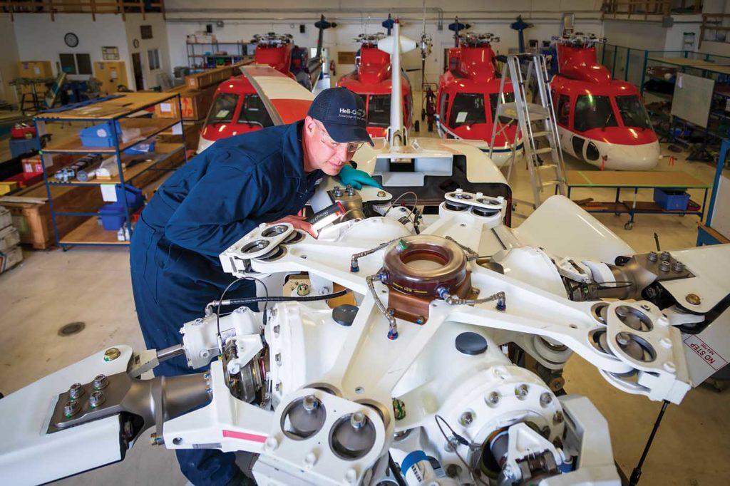 Heli-One aircraft maintenance engineer (AME) Josh Bonderoff performs a visual main rotor hub inspection on a Sikorsky S-76. Heath Moffatt Photo