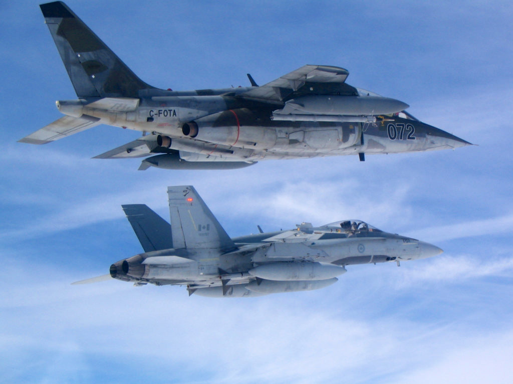 "Top Aces expects the ""workhorse"" Alpha Jet to remain the prime adversary fighter for the foreseeable future. That could involve more enemy role playing with new pilots as the Air Force seeks to introduce more advanced skills earlier in the training curriculum. Here, a Top Aces Alpha Jet (top) cruises alongside a Canadian CF-188 Hornet. Top Aces Photo"