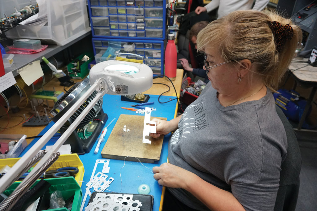 Elayna works on populating PC boards with real aircraft light bulbs for FDS light plates. Lisa Gordon Photo