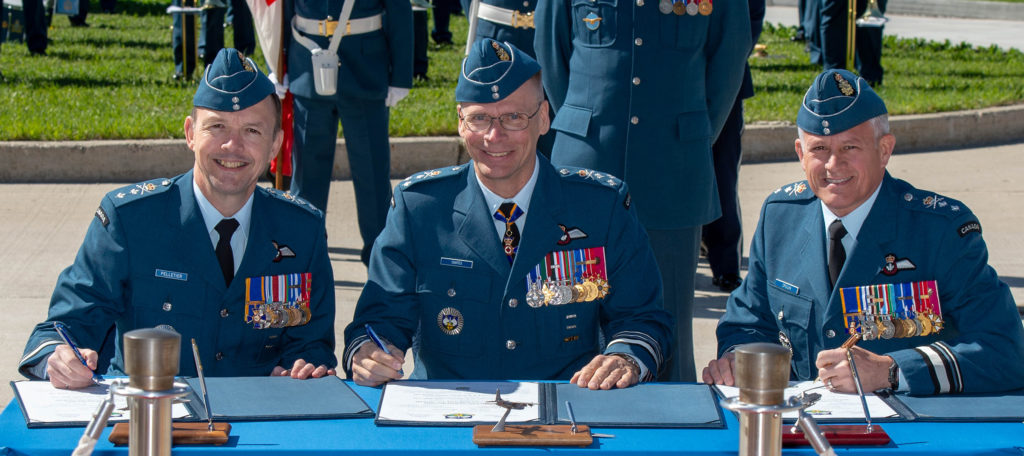 1 Canadian Air Division Commanding Officer, MGen Alain Pelletier, Deputy Commander North American Air Defense, LGen Christopher Coates and 1 CAD CO (outgoing), MGen Christian Drouin sign the Change of Command Scroll during the 1 CAD Change of Command ceremony. RCAF/Cpl Bryce Cooper Photo