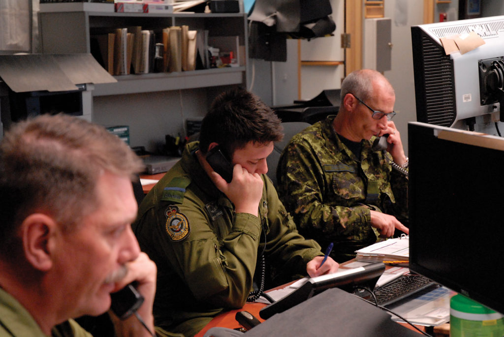 Maj Vern Greenway (left), one of the senior operations duty officers in the Combined Aerospace Operations Centre, works alongside duty defensive officers SL John Attwells and Capt David Weichel in the Air Operations Centre. DND Photo