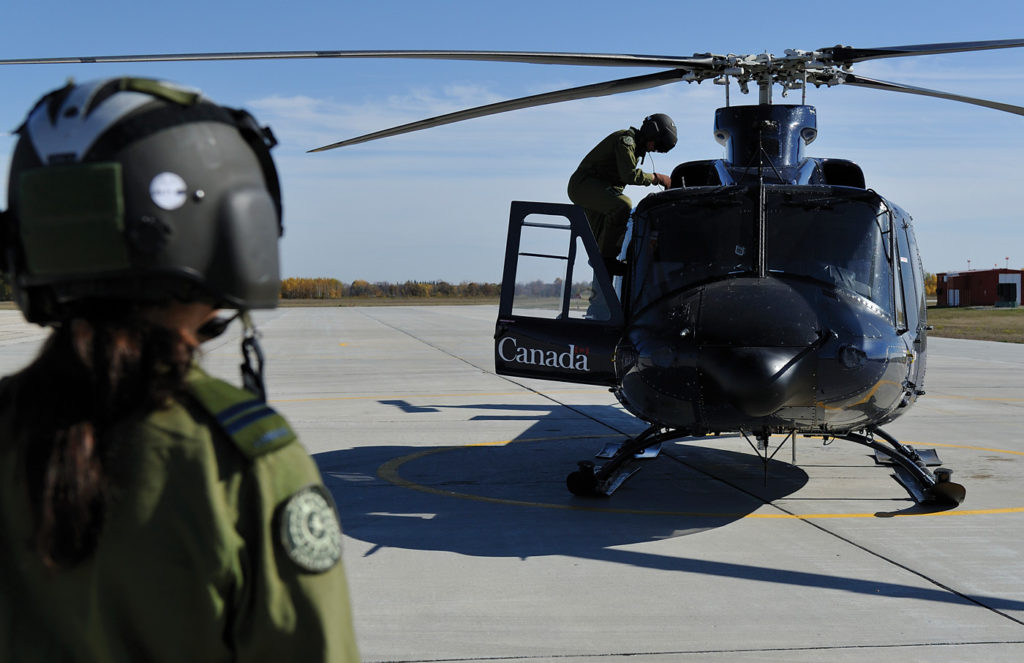 An instructor pilot supervises a student as he prepares a Bell 412 aircraft for flight at the Southport Aerospace Centre in Portage la Prarie. Cpl Vikcy Lefrancois Photo