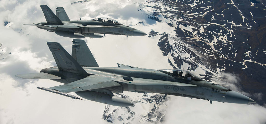 Two RCAF CF-188 Hornet fighters from 433 Tactical Fighter Squadron fly over Iceland during an Operation Reassurance surveillance mission in 2017. Cpl Gary Calve Photo