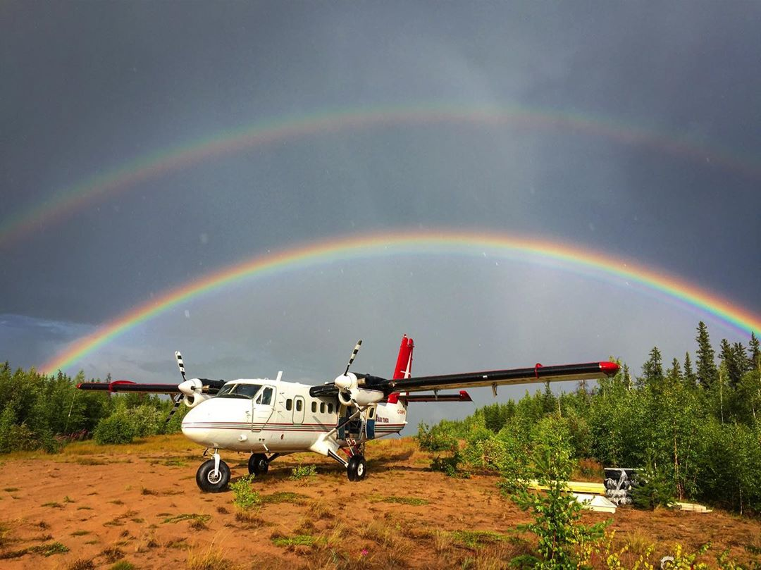 A Twin Otter sits dormant on the banks of Sparks Lake in the Northwest Territories as a double rainbow shines in the background. Photo submitted by Instagram user @thatotterdude by tagging @skiesmag.