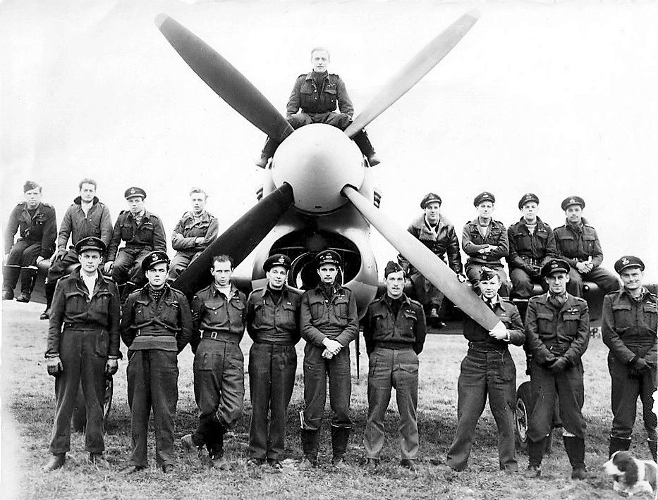 Squadron Leader David Fairbanks, DFC, is seen standing at far left in 1945 as commanding officer of 274 RAF Squadron, with a Hawker Tempest of the Squadron. Photo via the internet.