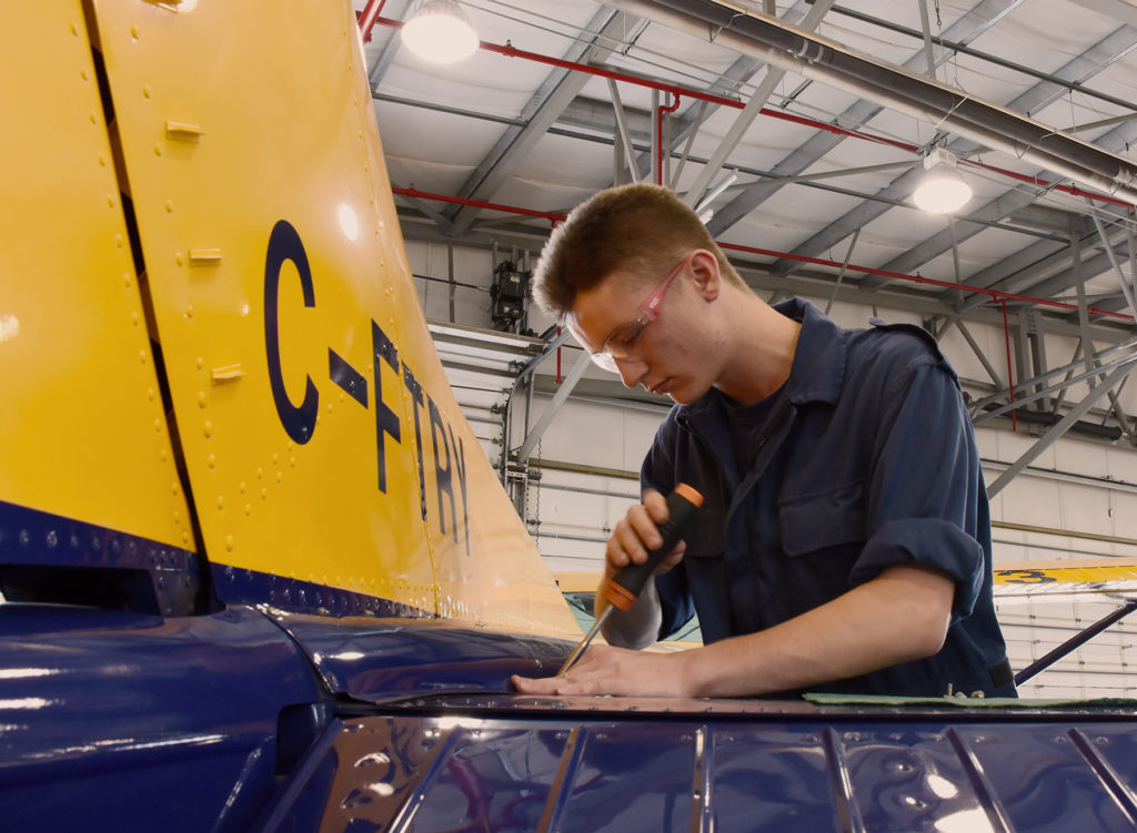 Cadet Warrant Officer Second Class Mitchell Mansfield works on the tail assembly of a tow plane at 442 Transport and Rescue Squadron hangar at Comox Cadet Flying Training Centre in Comox, B.C. Capt Angela Sargent Photo
