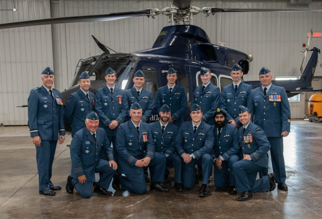 Graduates of the rotary wing course, along with school personnel, BGen Mario Leblanc (standing, left) and HCol Andy Fletcher (kneeling, left), gather for a photo after receiving their pilot wings. RCAF Photo