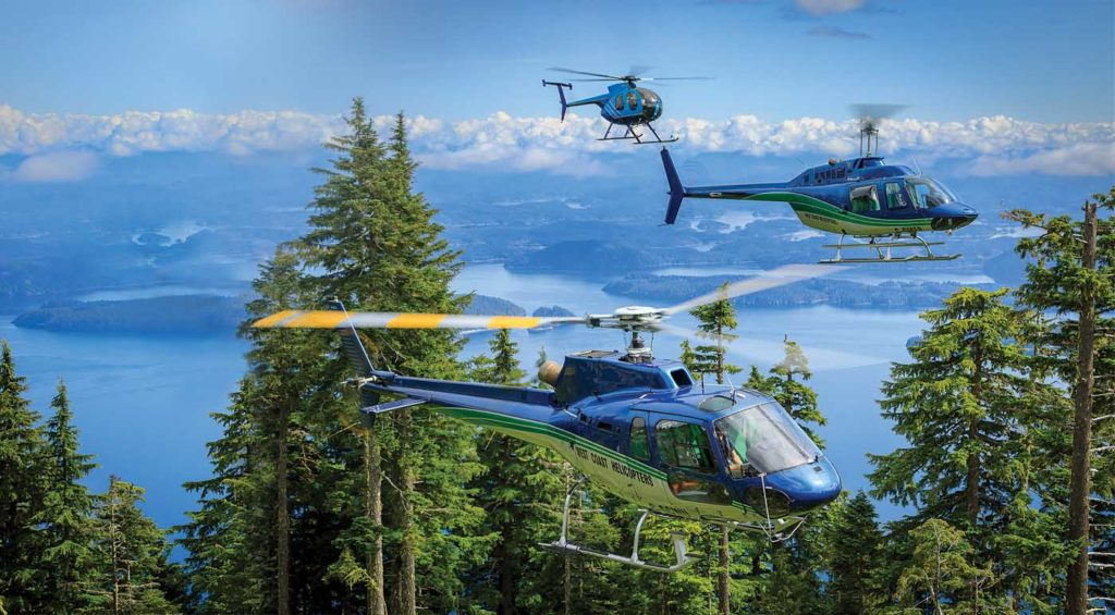 An MD 500, Bell 206 B JetRanger and AS350 B2 belonging to West Coast Helicopters fly over the spectacular coastline of northern Vancouver Island. Heath Moffatt Photo