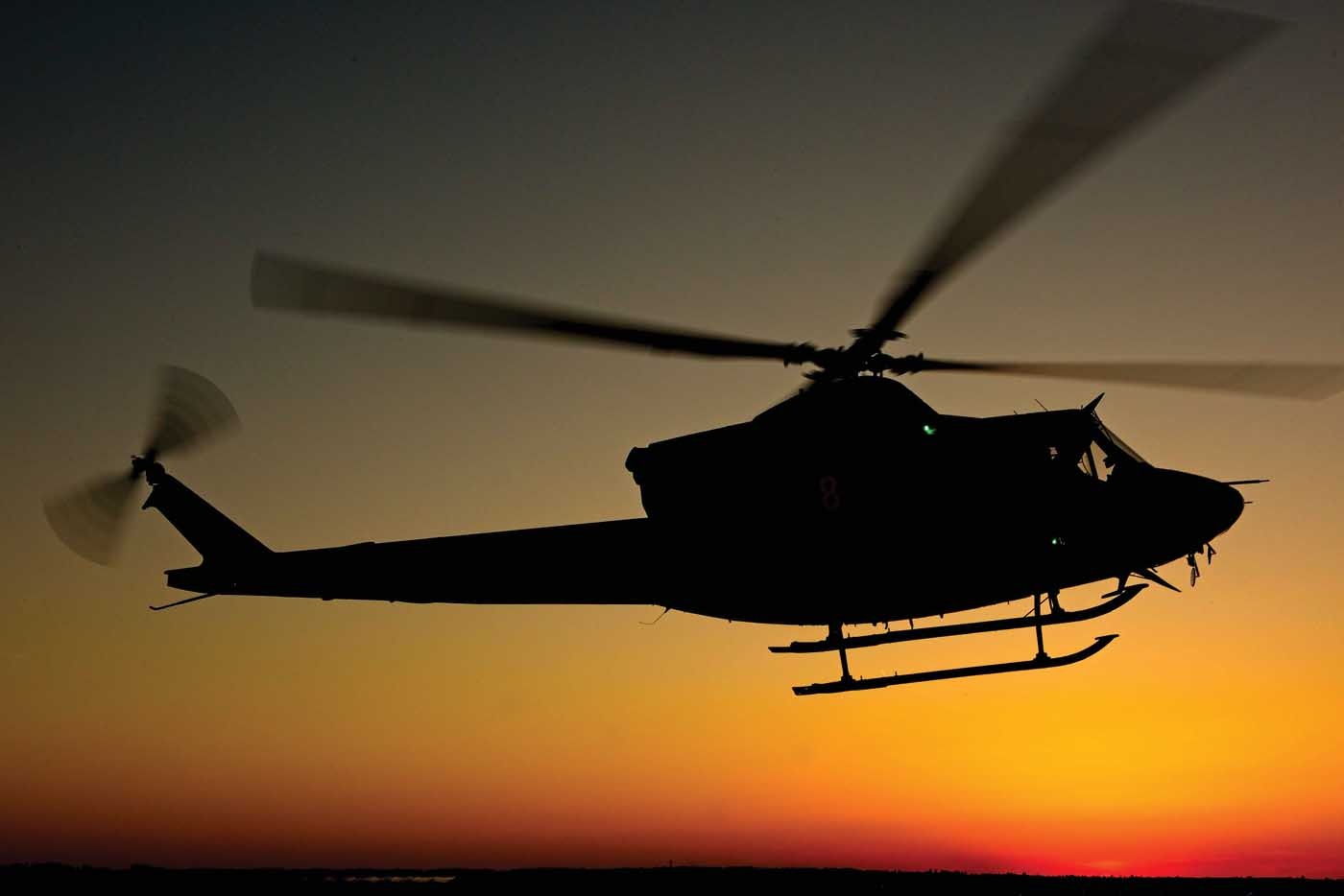 A Bell 412 flies at sunset with the distinctive outline of the BLR FastFin System in its tail. Mike Reyno Photo