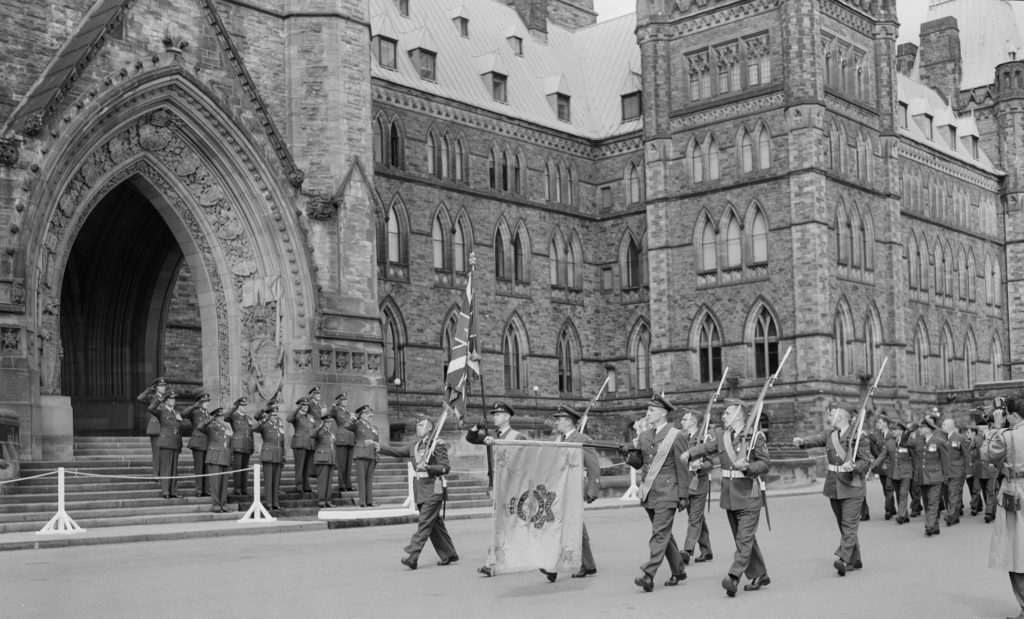 During the Battle of Britain parade held on Parliament Hill on September 16, 1956, the colour party marches past the saluting base in front of the Peace Tower. RCAF Photo
