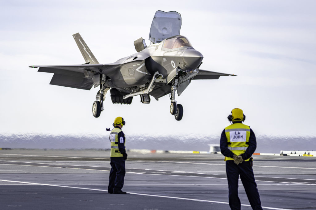 """Aircraft Handlers standby as an RAF F-35B Lightning II of 617 """"Dambusters"""" Squadron vertically lands on the deck of HMS Queen Elizabeth. Matt Haskell Photo"""