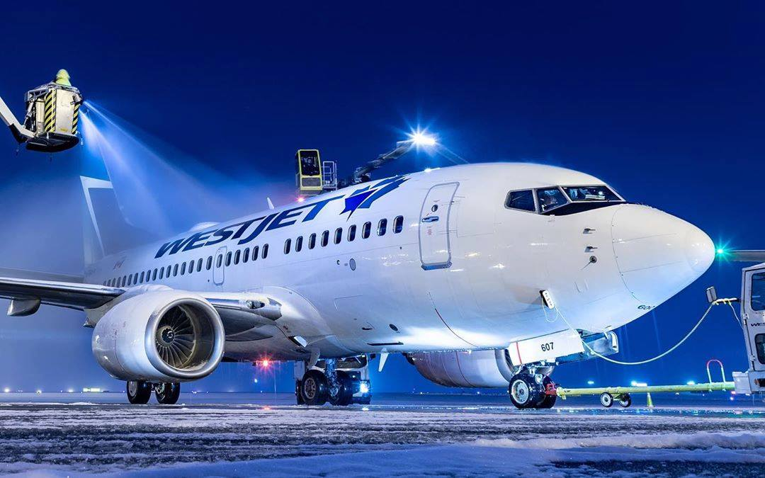 A WestJet Boeing 737-6CT gets de-iced at Calgary airport before departing to CYWG. Photo submitted by Instagram user @yyc_aviationphotography using #skiesmag