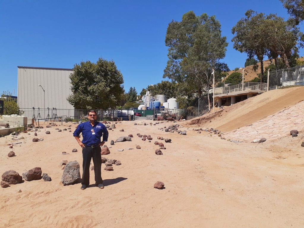Wilson Boynton stands in a rover testing field complete with varying sand and stone ground cover used to mimic Mars terrain for the testing of rover navigation and locomotion. Advanced Composites Training Press Release