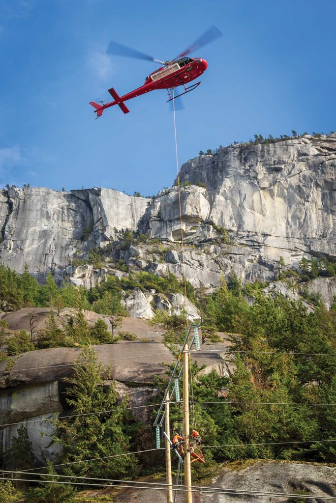 Blackcomb Helicopters pilot Jeff Stebnicki moves an Airbus AS355N TwinStar over a BC Hydro power pole. Line personnel are making final adjustments to a structure replacement project near Squamish, British Columbia. Heath Moffatt Photo