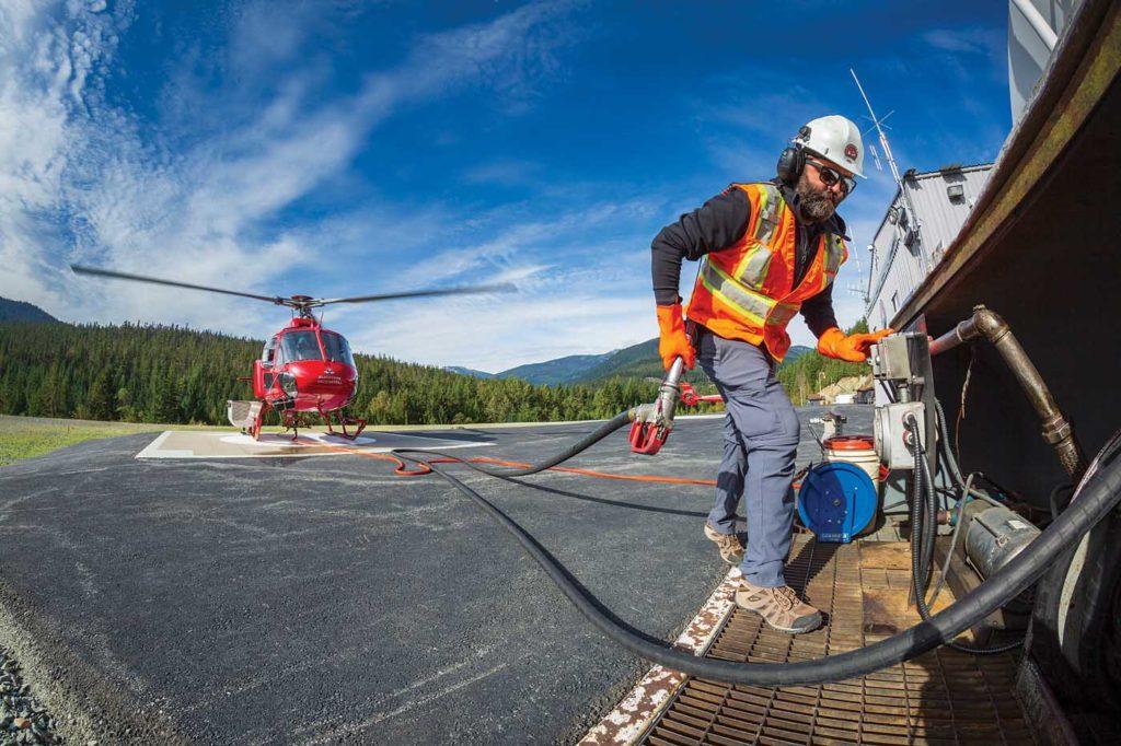 Ground crewmember Roland Stanley hot fuels an AS350 B3 at the Whistler heliport. Heath Moffatt Photo