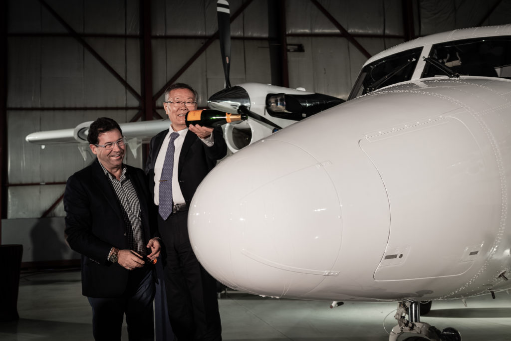 David Curtis, president and CEO of Viking Air, left, and Professor He Qinghua, chairman of Avmax parent company Sunward, christened the aircraft for good luck. The two aircraft will soon be departing for contractual work in Chad. Avmax Photo