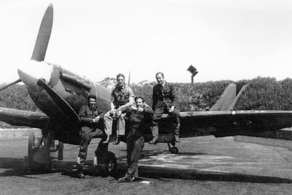 From left, PO Junius Lyman Edward Hokan, Sgt S.C. Creagh (Royal Australian Air Force), Sgt K. Edwards (Royal Air Force) and Sgt H. Fallon (RAF) pose with a Spitfire Mk. Vb from 610 Squadron. DND Photo