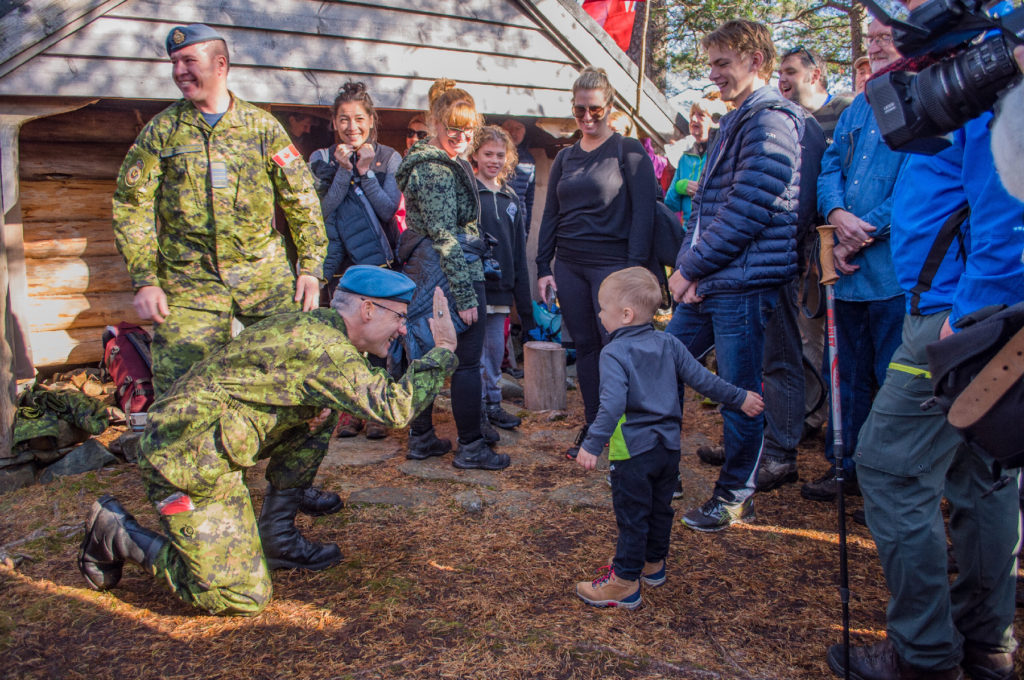 Chief WO Serge Harvey, squadron chief warrant officer of 407 Squadron, prepares to be high-fived by a toddler during his meeting with the latest generation of descendants of the Milorg, local residents, and the Canadian crew at a small wooden cabin named
