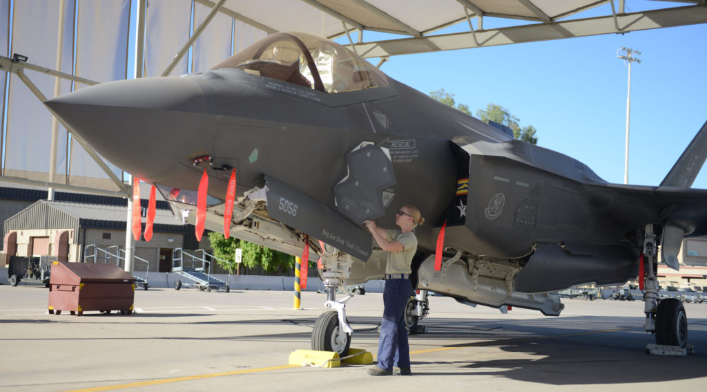 One F-35 technician equipped with a Portable Maintenance Aide, a laptop computer connected to the aircraft, is now required to do the same task that requires six maintainers on the F-16. USAF Photo