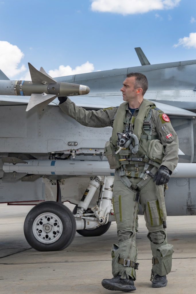 LCol Forrest Rock inspects the Royal Canadian Air Force CF-188 Hornet aircraft before a training flight during Operation Reassurance-Air Task Force Romania. LS Erica Seymour/RCAF Photo