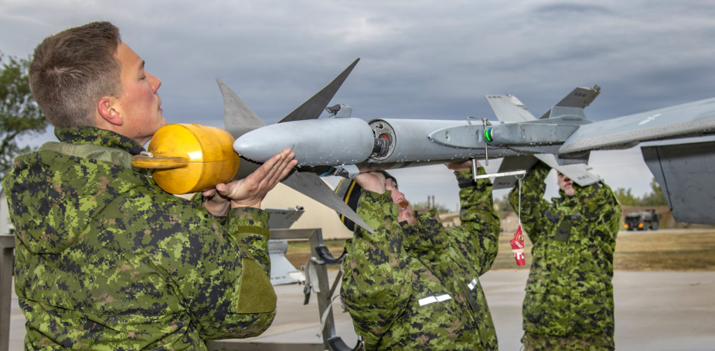 Air Weapons Systems Technicians, Cpl Benjamin Peddle (left), Cpl Zachery Bailie (center), and Cpl Robin Gagne (right) load an AIM-9 Captive Air Training Missile (CATM) on a Royal Canadian Air Force CF-188 Hornet aircraft. LS Erica Seymour/RCAF Photo
