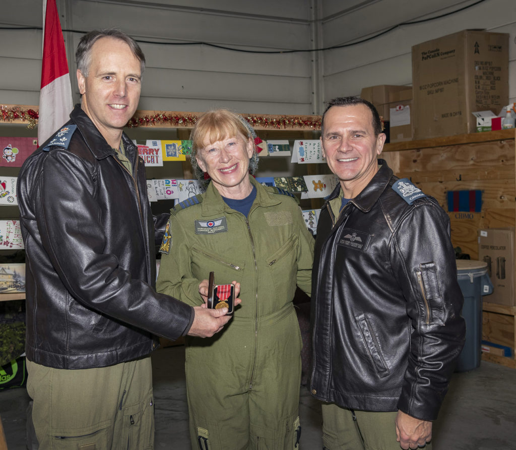 LGen Al Meinzinger, left, commander of the RCAF, accompanied by CWO Denis Gaudreault, right, RCAF command chief warrant officer, presents HCol Loreena McKennitt with the Canadian Forces Decoration, representing 12 years of honourable service, on Dec. 14, 2019. RCAF Photo