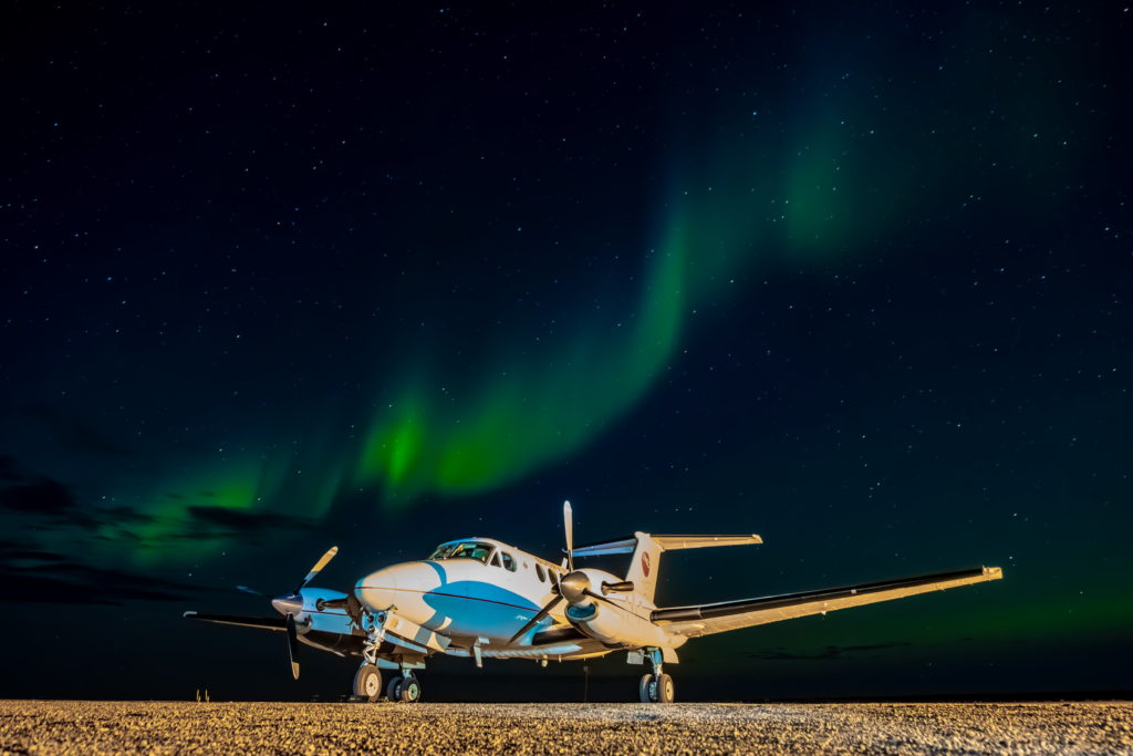 A Keewatin Air Beechcraft King Air 200 sitting under the northern lights. EIC Photo