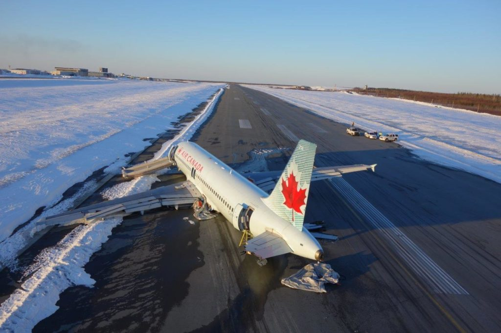 "According to the TSB report, the aircraft ""severed power lines, then struck the snow-covered ground about 740 feet before the runway threshold."" RCMP Photo"