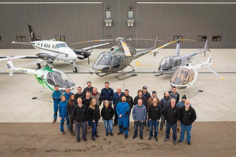 Staff from Synergy Aviation, Synergy Flight School and students stand in front of the companies' hangars and a selection of the aircraft shared by the two organizations. Heath Moffatt Photo
