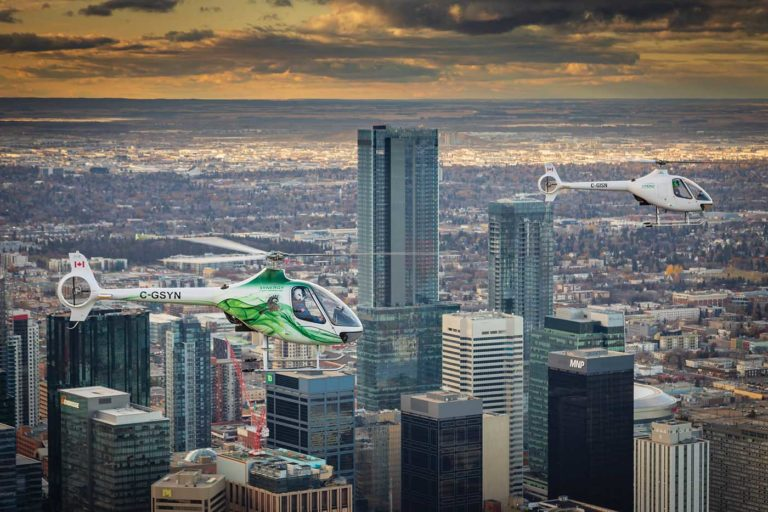 Two Hélicoptères Guimbal Cabri G2s, operated by Synergy Flight School, fly over downtown Edmonton, Alberta. The company is based on the edge of the Alberta capital, in the small settlement of Villeneuve. Heath Moffatt Photo