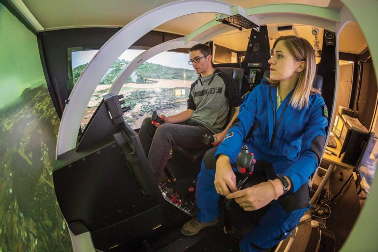 Instructor Ilona Inman (right) joins a student for a training session in Synergy's flight training device. Heath Moffatt Photo