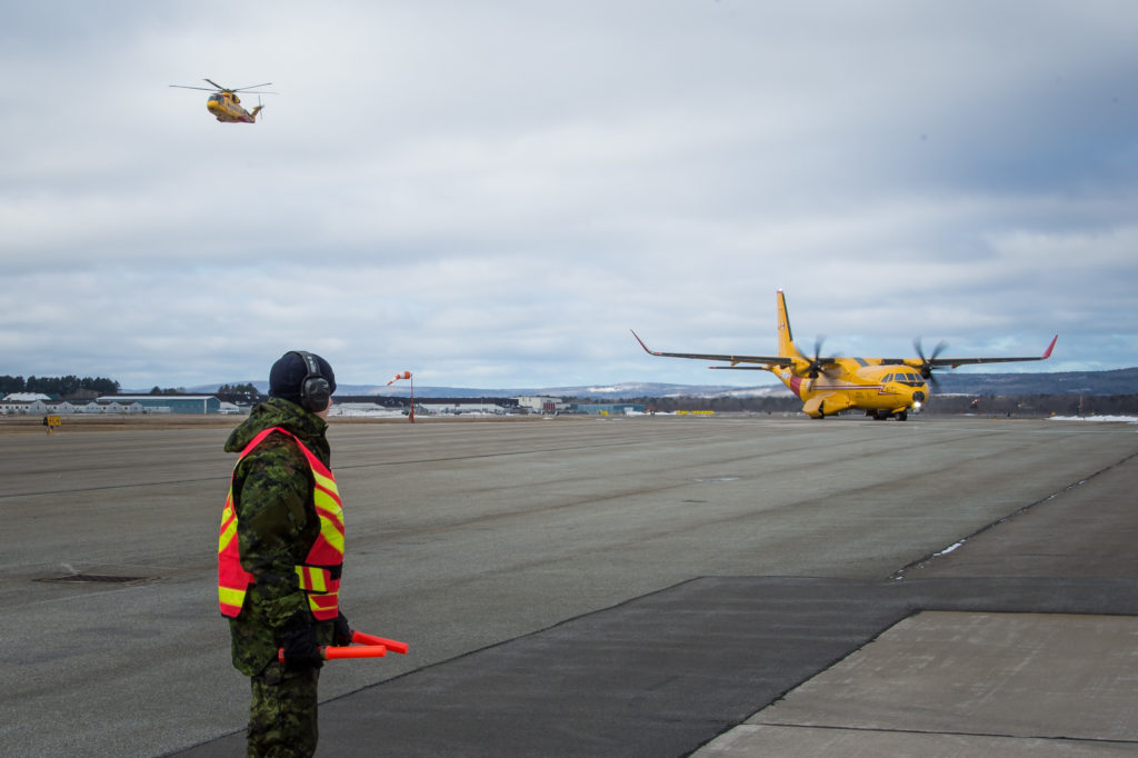 The new aircraft maintenance trainer fixed-wing search and rescue CC-295 taxis from the runway to 14 Hangar at 14 Wing Greenwood while a CH-149 Cormorant flies overhead. RCAF Photo