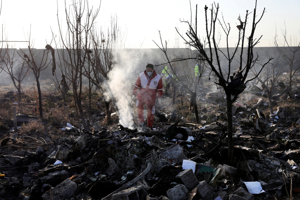 A rescue worker searches the area of the crash that happened just outside Tehran, Iran. AP Photo/Ebrahim Noroozi