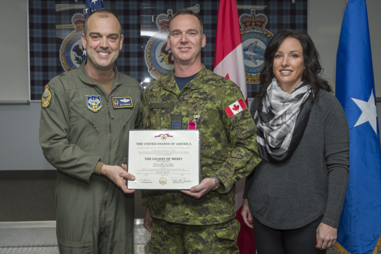 BGen Edward L. Vaughan, left, deputy commander Canadian NORAD Region, presents the Legion of Merit to LCol John Roper, Mission Support Squadron commanding officer, standing with Roper's wife, Lori. MCpl Alana Morin/RCAF Photo