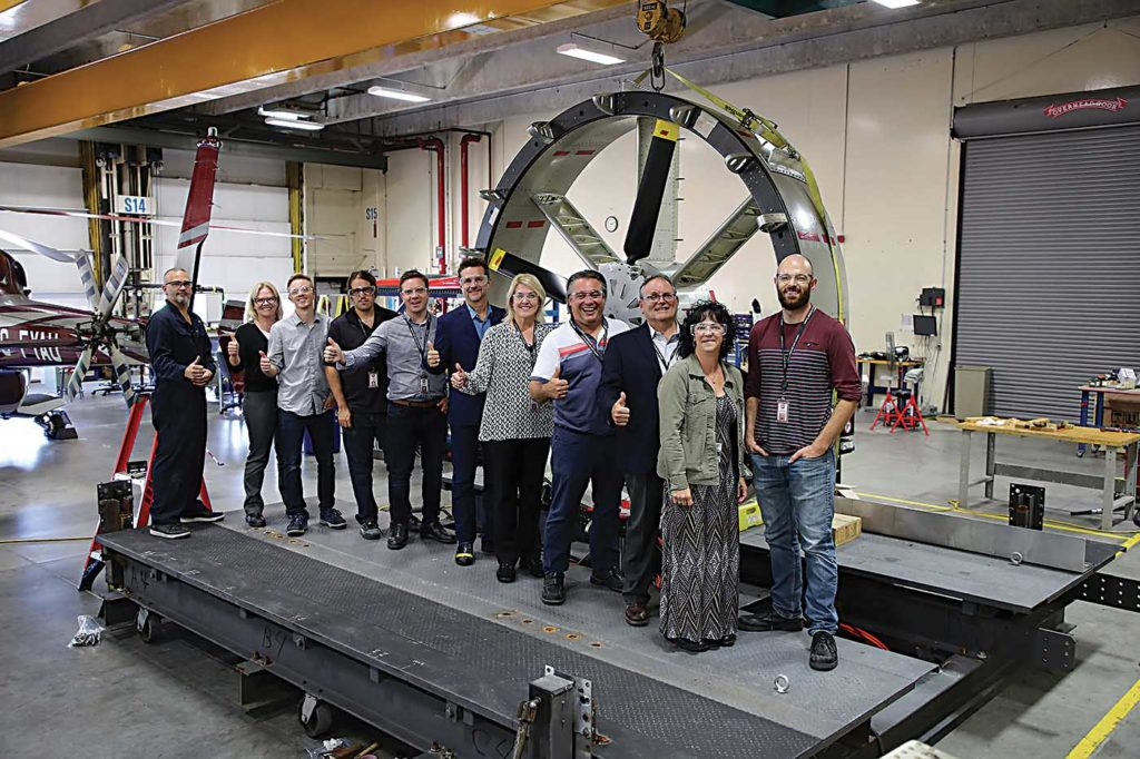 Members of Bell's innovation team stand in front of a ducted fan created for the manufacturer's Nexus eVTOL aircraft. The ducted fan was assembled in Mirabel and then taken to the National Research Council's wind tunnel in Ottawa for testing. Bell Photo