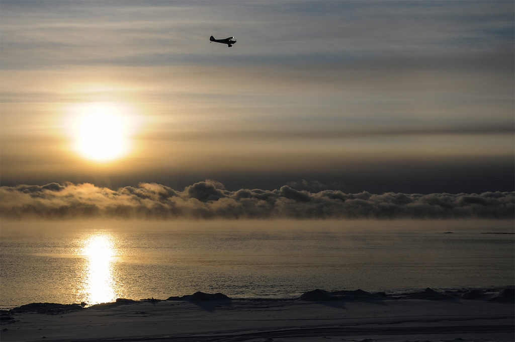 """Hoarfrost's Aviat A-1B Husky descends over McLeod Bay, on base leg for the small sand """"airstrip"""" Dave Olesen uses during freeze-up and breakup. Kristin Gilbertson Olesen Photo"""