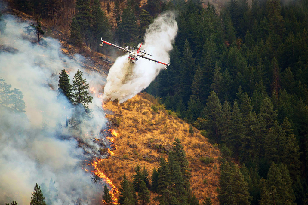 A Canadair CL-415 operated by Conair's U.S. division, Aero-Flite, drops water over a fire in California. U.S. Forest Service Photo