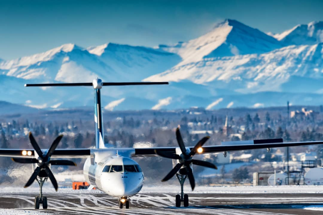 A stunning view in the background of this shot of a WestJet Encore Bombardier Q400 in Calgary. Photo submitted by Adrian Edwards (Instagram user @ace.yyc) by tagging @skiesmag.