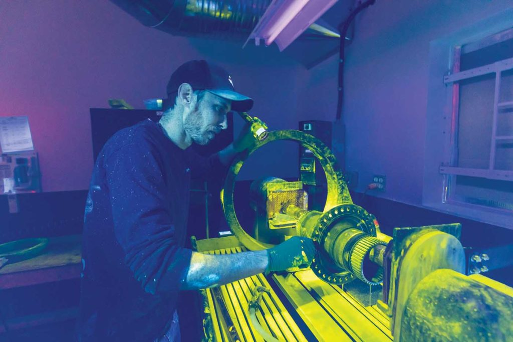 Alpine Aerotech NDT technician Travis Todevic examines various parts on a Magnetic particle bench inspection under black light. Heath Moffatt Photo